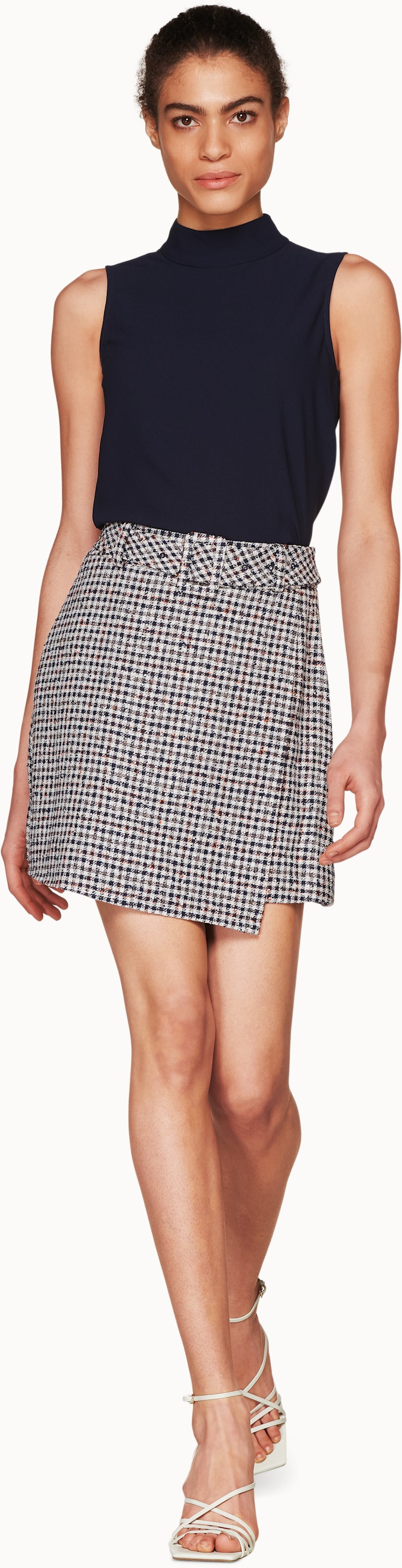 5729dcf5a4 Calvin Navy & Chocolate Checked Skirt $299 USD Tailored to an A-line fit  with a high rise waist, this Calvin mini wrap skirt features a  fabric-covered belt.